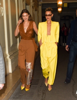 Gigi Hadid & Bella Hadid hold arms and laugh and smile as they are seen at 'The Americans In Paris' event at Paris fashion week